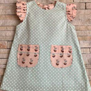 Vestido infantil, modelo trapézio, verde com poá branco; bolsos e mangas com estampa de corações