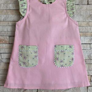 Vestido infantil, modelo trapézio, rosa, com bolsos e mangas em estampa floral. O tecido é tricoline 100% algodão